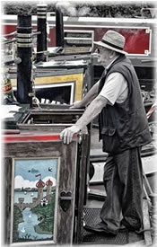 Man at the helm of a canal boat